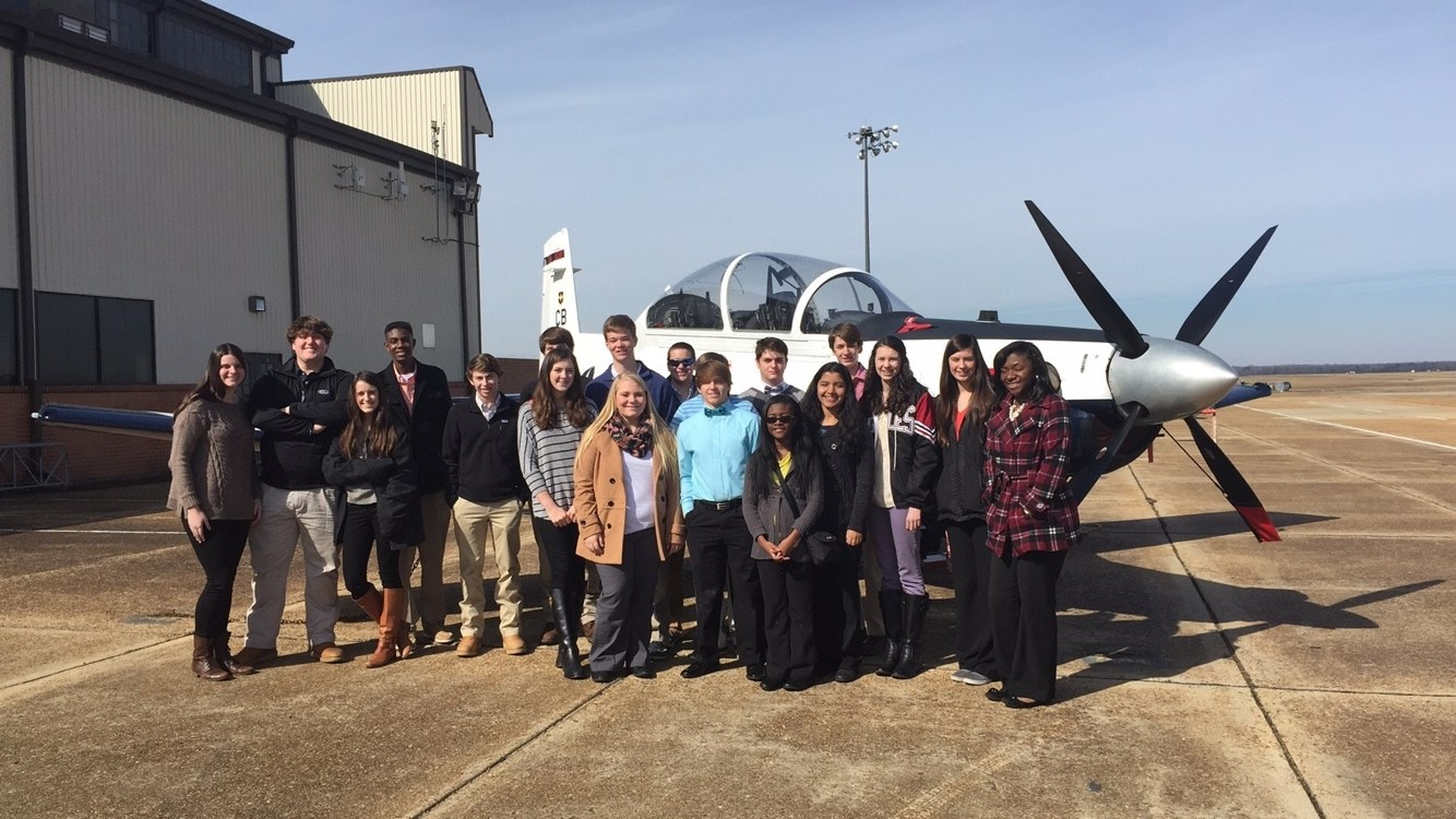 smiling people standing in front of prop airplane