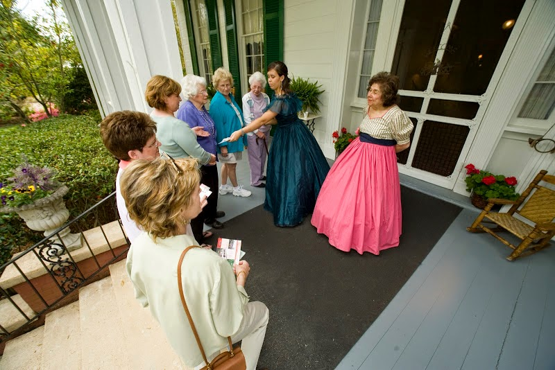 people in period dress standing on front porch of home