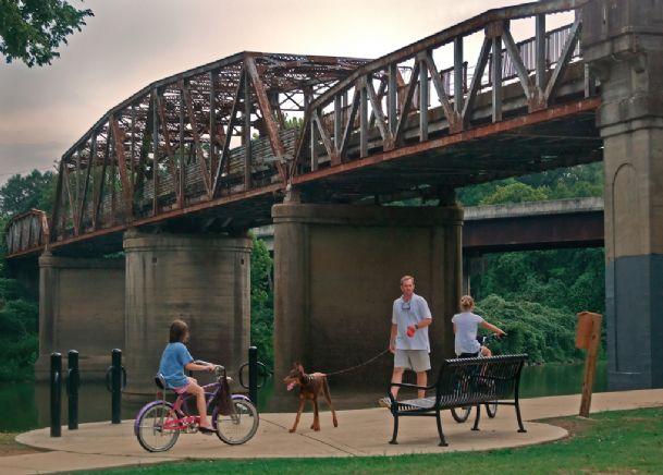people biking under bridge on path